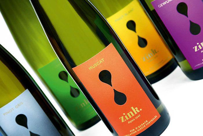 Les vins du domaine Zink sont dotés d'une étiquette aux couleurs joyeuses et au toucher soyeux, avec un sablier au centre en défonce (en découpe) pour créer un effet ludique pour les yeux: on voit à travers l'étiquette le niveau du vin dans la bouteille.